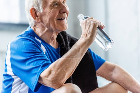 Photo pour Mise au point sélective du plaisir sportif senior avec serviette et bouteille d'eau au repos au gymnase - image libre de droit