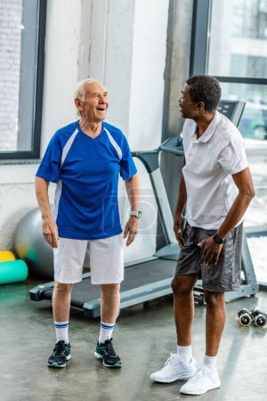 Photo for Cheerful multiethnic sportsmen talking to each other at gym - Royalty Free Image