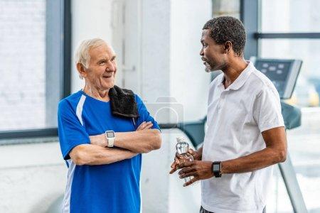 Foto de Deportistas maduros multiculturales hablando uno al otro durante el descanso en el gimnasio - Imagen libre de derechos