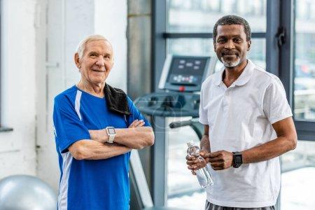 Foto de Felizes deportistas maduros multiculturales con smartwatches de pie en el gimnasio - Imagen libre de derechos
