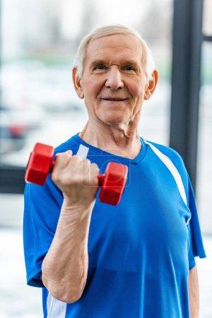 sportif senior souriant faisant de l'exercice avec haltère au gymnase