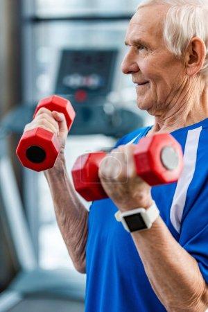 Photo pour Mise au point sélective du sportif senior avec smartwatch faire des exercices avec des haltères au gymnase - image libre de droit