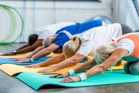 Photo for Selective focus of multicultural athletes synchronous exercising on fitness mats at gym - Royalty Free Image