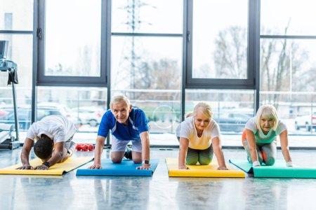 senior athletes making exercise on fitness mats at sports hall