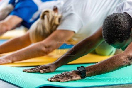Foto de Deportista afroamericano con smartwatch ejercer cerca de amigos en el gimnasio - Imagen libre de derechos