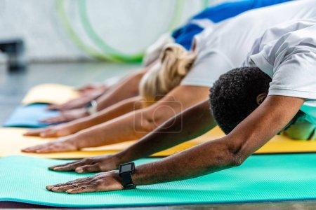 Foto de Enfoque selectivo del deportista afroamericano con smartwatch ejercer cerca de amigos en el gimnasio - Imagen libre de derechos