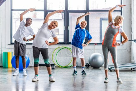 Photo for Happy multiethnic senior sportspeople synchronous exercising at sports hall - Royalty Free Image