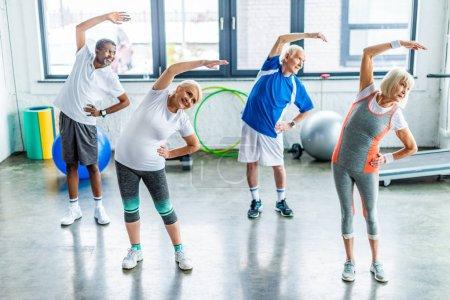 Photo pour Vue en angle élevé de sportifs âgés multiethniques faisant de l'exercice synchrone dans une salle de sport - image libre de droit