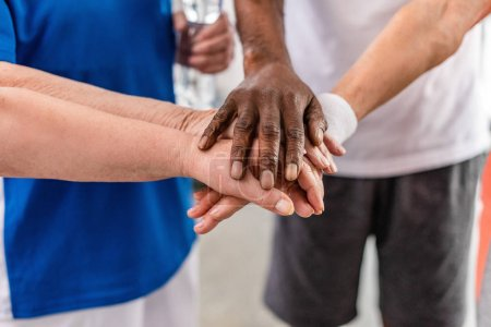 cropped shot of senior multiculutral sportspeople putting hands together at sports hall