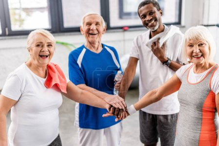 Photo for Laughing senior multiculutral sportspeople putting hands together at sports hall - Royalty Free Image