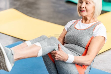 Photo for Selective focus of senior sportswoman exercising on fitness mat at gym - Royalty Free Image