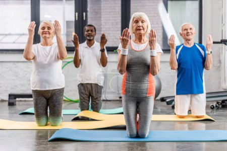 Photo for Senior multicultural sportspeople synchronous exercising on fitness mats at gym - Royalty Free Image