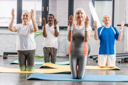 Photo for Multiethnic senior athletes synchronous exercising on fitness mats at gym - Royalty Free Image
