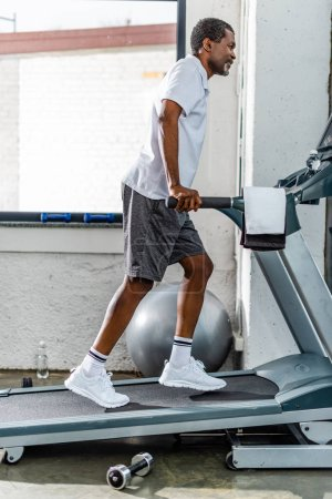 side view of african american man running on treadmill at gym