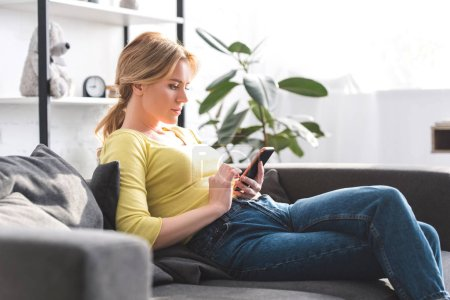 Photo for Side view of beautiful woman sitting on couch and using smartphone at home - Royalty Free Image
