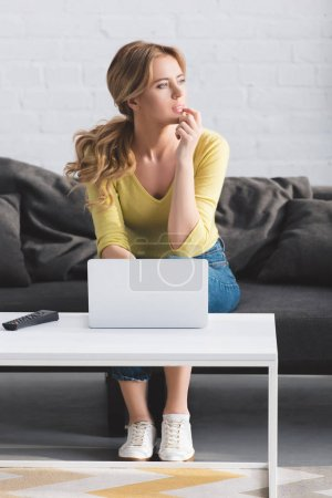 Photo for Thoughtful woman looking away while sitting on couch and using laptop - Royalty Free Image