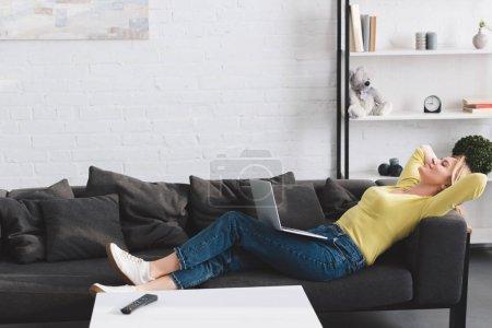 Photo pour Vue latérale de femme heureuse et détendue couchée avec un ordinateur portable sur le canapé - image libre de droit
