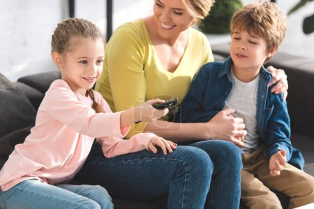 happy mother looking at kids using remote controller and watching tv at home