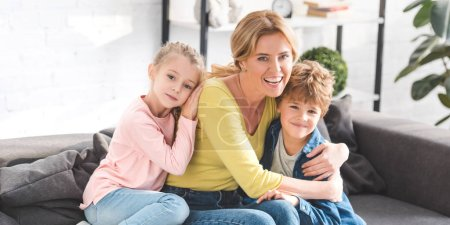 Photo for Happy mother with adorable children hugging and smiling at camera - Royalty Free Image