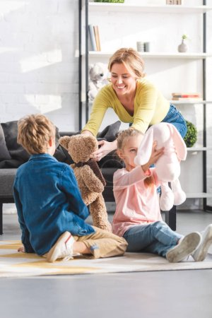 Photo for Happy mother and adorable little kids playing with toys at home - Royalty Free Image