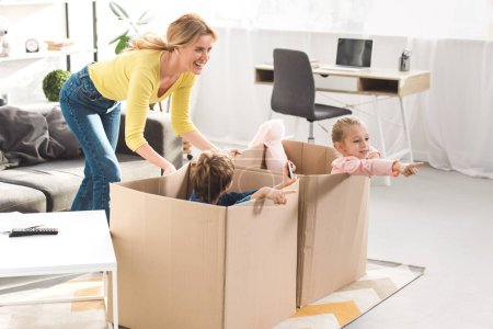 Photo for Happy mother playing with kids sitting in cardboard boxes at home - Royalty Free Image