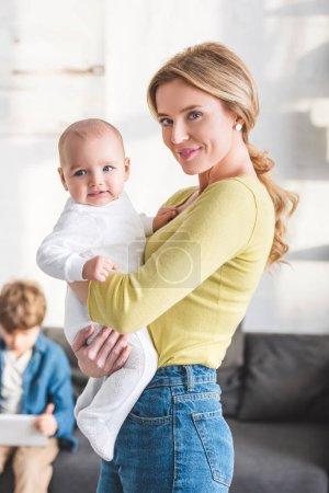 Photo pour Belle mère heureuse tenant adorable enfant en bas âge et souriant à la caméra - image libre de droit