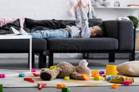 Foto de Juguetes en la alfombra y niño acostado en el sofá detrás de - Imagen libre de derechos