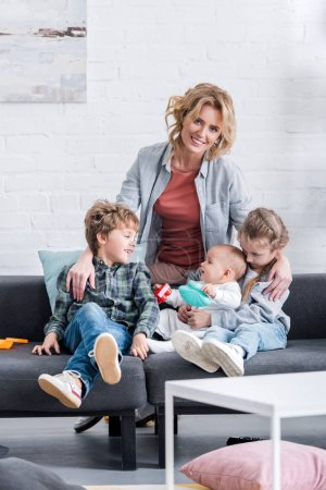 Photo for Happy mother smiling at camera while spending time with three adorable children at home - Royalty Free Image