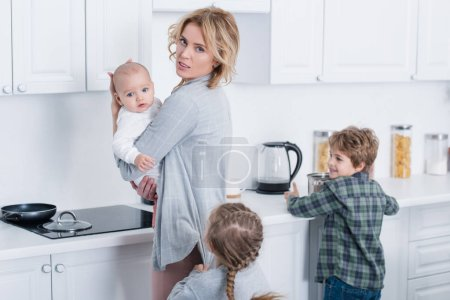 Photo for Tired mother holding infant child and looking at camera while naughty children playing in kitchen - Royalty Free Image