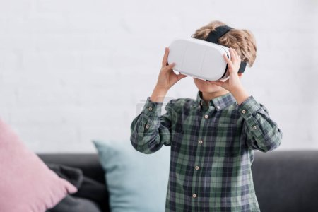 Photo for Adorable little boy using virtual reality headset at home - Royalty Free Image