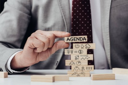 cropped view of man holding brick with word 'agenda' over wooden blocks with icons