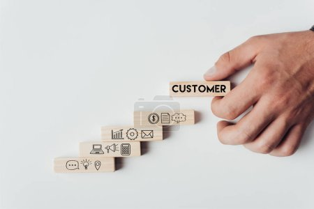 Photo for Cropped view of man holding wooden block with word 'customer' on top of wooden bricks with icons isolated on white - Royalty Free Image