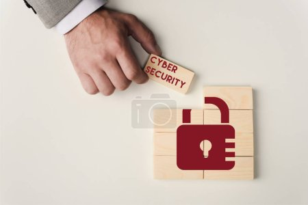 Photo for Partial view of man holding brick with 'cyber security' lettering over wooden blocks with lock icon isolated on white - Royalty Free Image