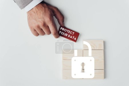 partial view of man holding brick with 'protect your data' lettering over wooden blocks with lock icon isolated on white