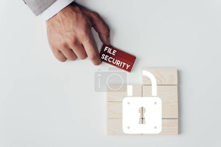 partial view of man holding brick with 'file security' lettering over wooden blocks with lock icon isolated on white