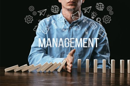 Photo for Cropped view of man preventing wooden blocks from falling with word 'management' and icons on foreground - Royalty Free Image