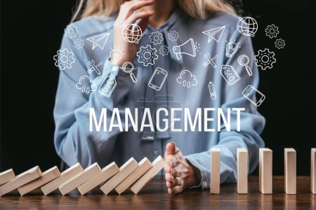 Photo for Cropped view of woman preventing wooden blocks from falling with word 'management' and icons on foreground - Royalty Free Image