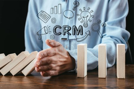 close up view of woman preventing wooden blocks from falling with word 'crm' and icons on foreground
