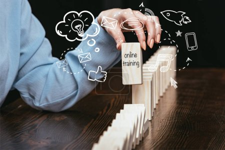 cropped view of woman picking block with words 'online training' out of wooden bricks, icons on foreground