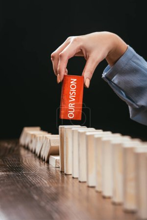 Photo for Partial view of woman picking red wooden brick with word 'our vision' from row of blocks on desk isolated on black - Royalty Free Image