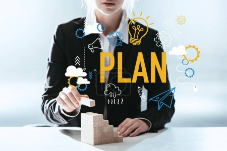 Photo for Cropped view of woman building career ladder with wooden blocks, icons and 'plan' lettering on foreground - Royalty Free Image