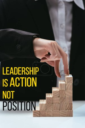 cropped view of woman climbing with fingers wooden career ladder, 'leadership is action not position' lettering on foreground