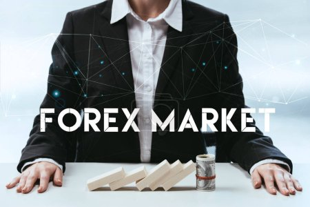 cropped view of businesswoman with wooden blocks and money roll on table and 'forex market' lettering on foreground