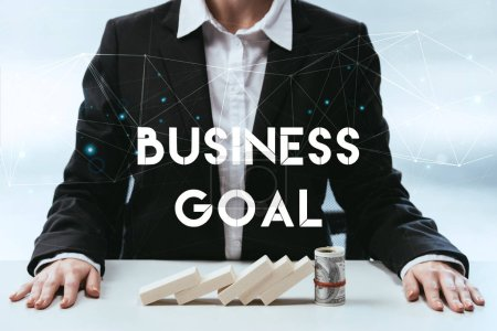 Photo for Cropped view of businesswoman with wooden blocks and money roll on table and 'business goal' lettering on foreground - Royalty Free Image