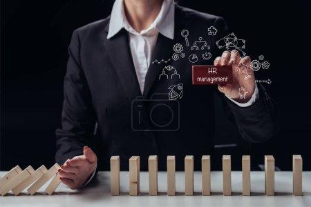 Photo pour Recadrée vue de femme d'affaires détenant des briques rouges avec des mots «Gestion des ressources humaines», tout en évitant les blocs de bois de tomber, icônes sur le premier plan - image libre de droit