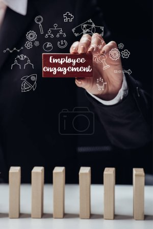 cropped view of woman holding red wooden brick with words 'employee engagement' isolated on black, icons on foreground