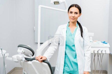 Photo pour Dentiste attrayant debout près de la chaise dans la clinique dentaire - image libre de droit