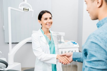 Photo for Smiling female dentist shaking hands with  african american patient - Royalty Free Image
