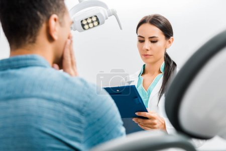 Photo for Selective focus of female dentist looking at clipboard and standing near african american patient with toothache - Royalty Free Image