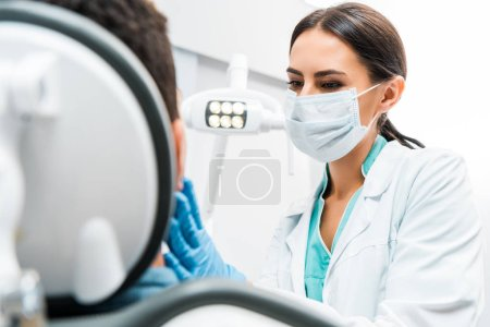 Photo for Female dentist in mask examining patient - Royalty Free Image